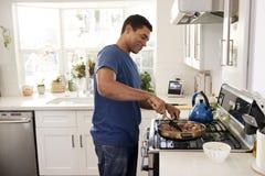 Posição afro-americano adulta nova do homem na cozinha que cozinha no hob, usando uma espátula e uma frigideira, opinião de lado, imagem de stock