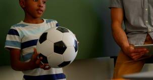 Posição afro-americano da estudante com futebol na sala de aula na escola 4k video estoque