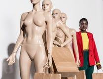 posição afro-americano da mulher na fileira com os manequins que guardam sacos de papel imagens de stock