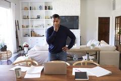 Posição afro-americano milenar do homem na tabela na sala de jantar que olha para baixo em sua tela de laptop imagens de stock royalty free