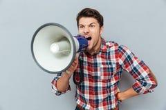 Posição agressiva furioso e gritaria do homem novo com altifalante Fotos de Stock