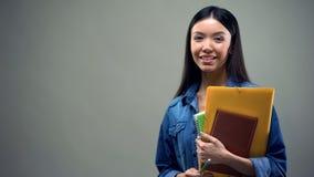 Posição asiática com cadernos, programa da senhora da troca do estudante, fundo cinzento foto de stock royalty free