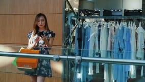 Posição asiática da mulher com smartphone em uma alameda filme