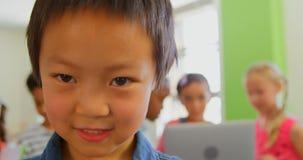 Posição asiática feliz da estudante em uma sala de aula na escola 4k vídeos de arquivo
