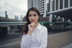 Posição asiática nova segura da mulher e levantamento de pensamento no fundo público de construção urbano foto de stock