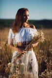 Posição atrativa da jovem mulher que levanta no campo da grama alta no por do sol imagens de stock