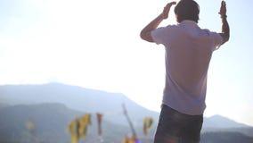 Posição bem sucedida nova do homem de negócios sobre uma montanha com a dança ascendente rised das mãos que aprecia o momento no  vídeos de arquivo