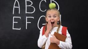 Posição bonita da estudante perto do quadro-negro com a maçã na cabeça, ideia brilhante video estoque