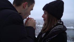 Posição bonita da jovem mulher e do homem na ponte perto do rio na roupa do inverno O homem aquece as mãos da senhora que respira vídeos de arquivo