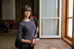 Posição bonita da jovem mulher na janela com o telefone fotografia de stock