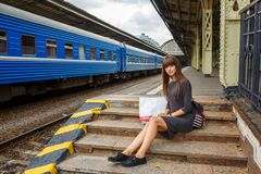 Posição bonita da jovem mulher na plataforma do conceito do curso da estação de trem imagens de stock