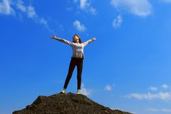 Posição bonita da moça na parte superior da montanha e das mãos guardar acima sobre o fundo do céu azul imagens de stock royalty free