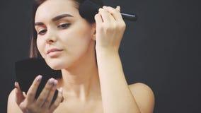 Posição bonita nova da menina em um fundo preto Durante isto, derrama o pó enfrenta em geral com uma escova que olha dentro video estoque
