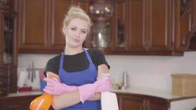 Posição bonita nova da mulher na cozinha com as mãos cruzadas que guardam as garrafas do detergente, olhando na câmera vídeos de arquivo