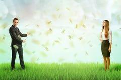 Posição cada um do homem de negócios e da mulher de negócios no lado diferente do gramado verde com chuva das notas de dólar no a imagem de stock royalty free