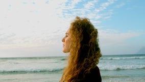 Posição caucasiano nova pensativa da mulher na praia na luz do sol filme