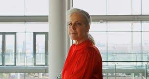 Posição caucasiano superior da mulher de negócios no prédio de escritórios 4k video estoque