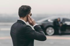 posição considerável da escolta e mensagem de escuta com fone de ouvido da segurança imagem de stock