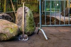Posição contra uma rocha em um canteiro de obras, fundo movente à terra da pá da indústria imagens de stock royalty free