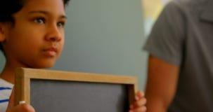 Posição da estudante com a ardósia do giz na sala de aula na escola 4k vídeos de arquivo