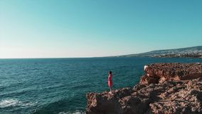 Posição da jovem mulher em penhascos rochosos no vestido vermelho com mãos distante no ar, vestido que bate no vento Apreciação f vídeos de arquivo