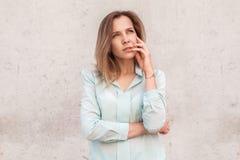Posição da jovem mulher isolada na parede que olha de lado pensativa fotografia de stock