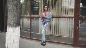 Posição da jovem mulher para beber o café, na frente das janelas espelhadas outdoor vídeos de arquivo