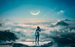 Posição da menina do surfista acima das nuvens que sonham sobre o inchamento fotografia de stock royalty free