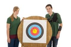 Posição da menina e do menino além do alvo do tiro ao arco Fotos de Stock Royalty Free