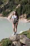 A posição da menina em uma pedra em uma inclinação de montanha olha o sol imagem de stock