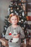Posição da menina na árvore de Natal e guardar um cavalo do brinquedo Está vestindo uma camiseta cinzenta fotografia de stock