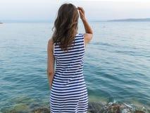 Posição da menina na costa e vista do mar fotos de stock royalty free