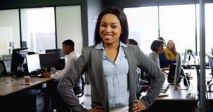 Posição da mulher de negócios com mãos no quadril no escritório 4k vídeos de arquivo