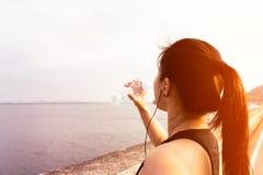Posição da mulher do esporte na baía e na água potável após consecutivamente foto de stock royalty free