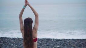 Posição da mulher da ioga em uma costa que olha o mar video estoque
