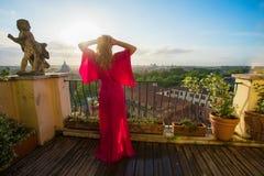 Posição da mulher no balcão que negligencia Roma cedo na manhã imagens de stock