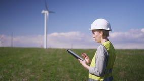 Posição da mulher perto do moinho de vento e informação da verificação na tabela vídeos de arquivo