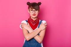 Posição de cabelo preta positiva sincera da menina isolada sobre o fundo cor-de-rosa no estúdio, cruzando seus braços, olhando di imagens de stock royalty free