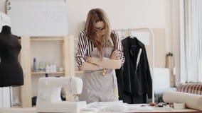 Posição de Caucasian da costureira fora de seu local de trabalho com seus braços dobrados Sorriso e fala com o alguém atrás do vídeos de arquivo