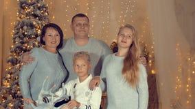 Posição de sorriso da família no fundo da árvore de Natal na sala de visitas acolhedor filme