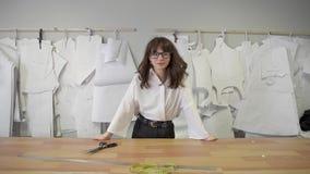 Posição de sorriso do desenhador de moda fêmea no fundo dos testes padrões de papel video estoque
