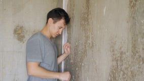Posição deprimida irritada do homem perto da parede e dos punhos da batida filme