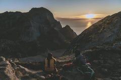 Posição do alpinista da mulher na rocha da montanha máxima no por do sol Montanha de Ryten, Noruega imagens de stock