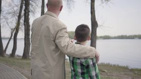 Posi??o do av? e do neto no riverbank, olhando na ?gua, apontando na dist?ncia O homem abra?a a crian?a perto video estoque