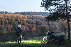 A posi??o do cavaleiro com motocicleta da aventura, motociclista, um motorista do velomotor olha, far?is sobre, floresta da noite imagem de stock royalty free