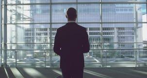 Posição do homem de negócios com bagagem na entrada no escritório 4k video estoque