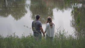 Posi??o do homem novo e da mulher na lagoa e olhar na dist?ncia que guarda as m?os video estoque