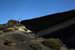 Posição do homem novo em uma montanha e renúncia foto de stock royalty free