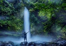 Posição do homem novo perto da cachoeira de Sawer imagens de stock royalty free