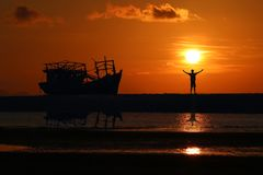 Posição do homem perto do barco quebrado velho abandonado na praia no por do sol foto de stock